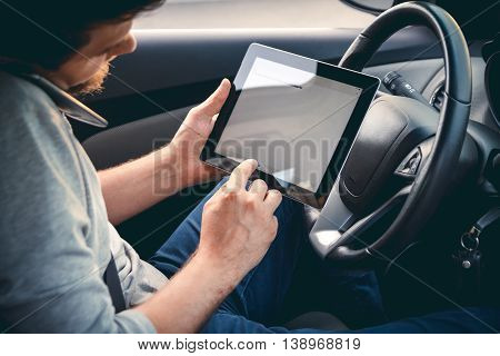 Young man driving a car with a tablet in hand, talking on mobile phone. Multitasking. Safe driving concept