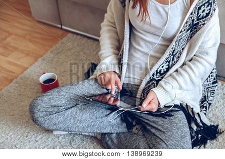 Woman in home cozy clothes sitting on the carpet near the sofa using a tablet with headphones, drinking coffee from a red cup. Online education concept. e-learning.