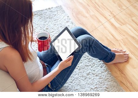 Woman in jeans sitting on the carpet near the sofa using a tablet, drinking coffee from a red cup. Online education concept. e-learning.