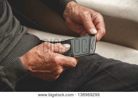 Senior sitting on a sofa with mobile phone in hand