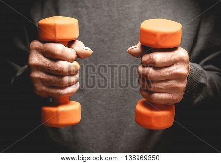 Orange dumbbells in the hands of an elderly man. Sports retired. Photo in low key