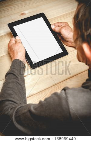 Senior sitting at a wooden table  with a tablet in hands. Online education retirement concept. e-Learning. mock up. Photo in low key