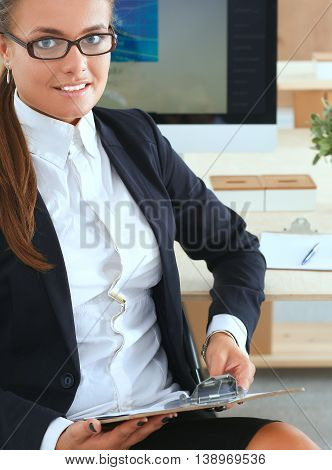 Young woman working in office, sitting at desk.