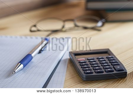 Workplace Accountant. Notepad In The Box With A Pen, Calculator, And Glasses On A Wooden Table In Th