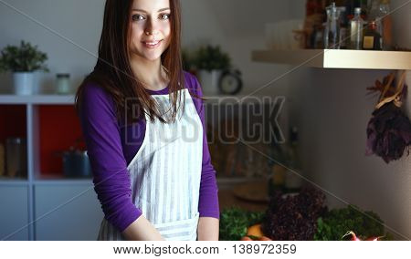 Young woman standing in her kitchen near desk with shopping bags.