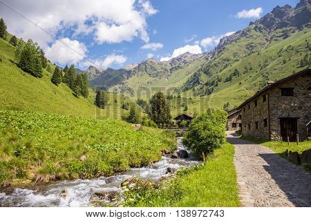 mountain panorama with creek and stone chalet - Ponte di Legno Italy