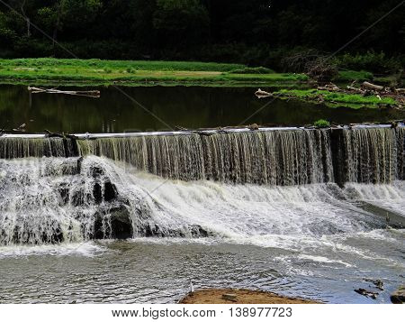 Waterfall flowing over an old dam with island background