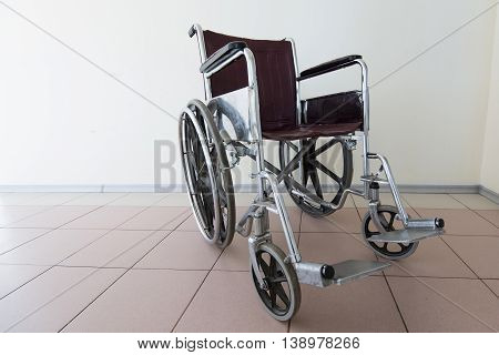 Empty wheelchair stands in patient rooms at hospital.