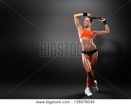 Portrait of beautiful smiling sportswomen is isolated on a dark background with a clipping path. Healthy lifestyle and fitness. Personal trainer.