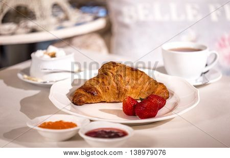 Classic Croissant with strawberries and coffee and tea