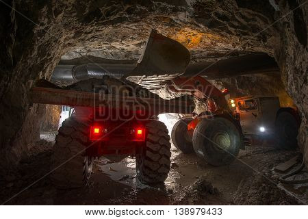 Loading truck with golden ore underground. russia.