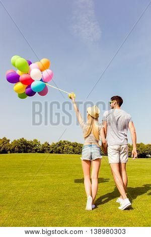 Back View Of Two Friends Walking In Park With Balloons