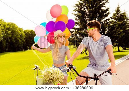 Happy Positive Young Couple On Bicycle In A Summer Park With Balloons And Flowers