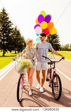 Portrait Of Happy Couple In Love Walking With Bikes And Balloons