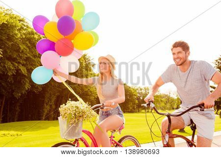 Portrait Of Two Happy Lovers Riding Bicycles With Balloons