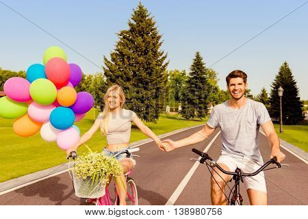 Happy Young Lovely Couple In Love Cycling And Holding Hands