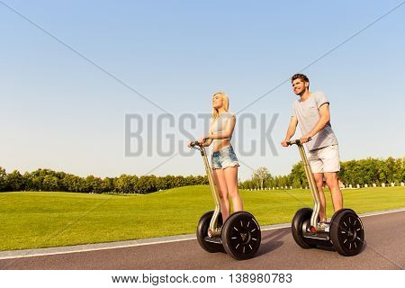 Young Cheerful Couple In Love  Driving Segways And Smiling In Park