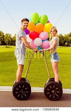 Portrait Of Happy Young Lovers With Balloons Using Segway In Park