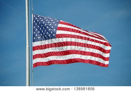 Shiny and silky American flag flying half mast against bright blue sky