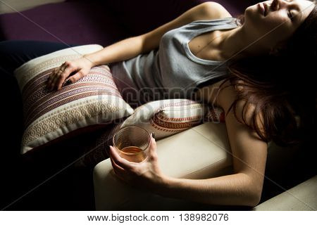 sad lonely woman drinks alcohol in the dark. Glass in sharp focus. female alcoholism.