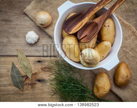 Fresh Organic Potatoes In Hemp Sake Bag With Ingredients And Herbs On Rustic Wooden Table Preparatio