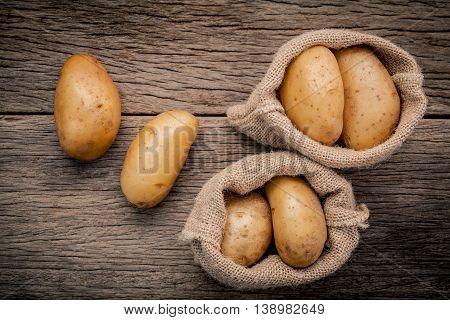 Fresh Organic Potatoes In Hemp Sake Bag On Rustic Wooden Background. Row Organic Potatoes  On Old Wo