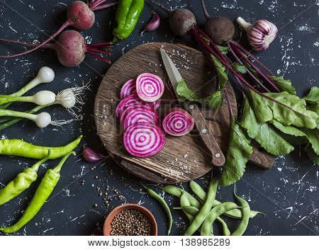 Beets peppers onions green beans spices on a dark background. Fresh garden vegetables. Vegetarian detox diet food