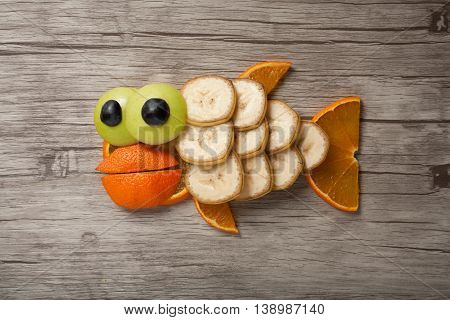 Fish made of orange and banana on wooden plank