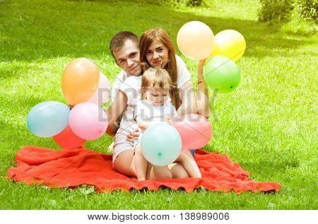 parents spend the weekend with their young daughter. with balloons