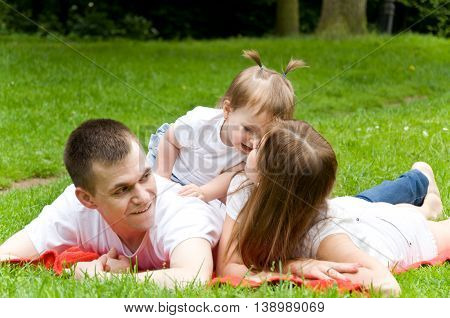 parents spend the weekend. daughter whispering something in the ear of her mother. Dad listens carefully to them