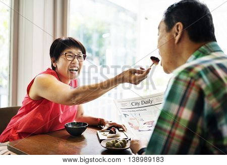 Elderly Senior Couple Playful Feeding Cafe Concept