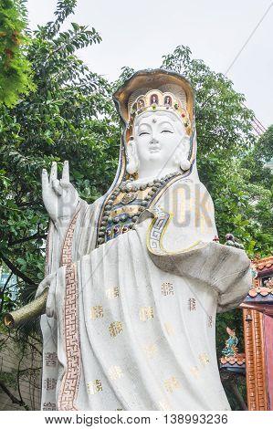 REPULSE BAY HONG KONG - MAY 23: The white statues of Kwun Yam with green leaves and bright sky as background at Kwun Yam temple on May 23 2016 in Repulse Bay Hong Kong.
