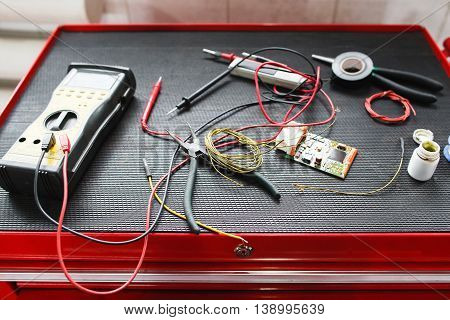 Equipment for electronic maintenance of car. Multimeter with necessary cables and connectors on electrician toolbox in garage, professional testing facilities