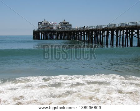 Malibu pier and waves with beautiful blue sky and ocean.