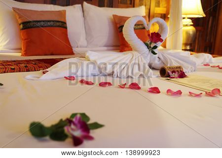 Honeymoon Bed Suite decorated with flowers and towels. Interior Of Bedroom Of Luxury Hotel Suite.