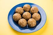 sesame laddu or tulgul or til gul laddu or ladu, favourite sweet dish in Makar Sankranti Festival in India, 14 january, indian festival sweets, served in triangle plate poster
