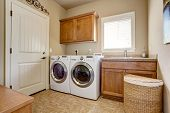 Laundry room with washer and dryer. Wooden cabinets and tile floor poster