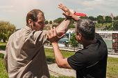 Kapap instructor demonstrates self defense techniques against a knife attack poster