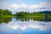 Beautiful landscape with blue sky and white clouds reflected in the clear river water. Wooded waterside of a mountain lake. Summer idyllic landscape. poster