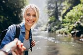 Portrait of happy young woman holding hand of her boyfriend while walking by forest creek. Woman enjoying a hike in nature with her boyfriend. Point of view shot of couple hiking in nature. poster
