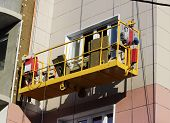 construction suspended yellow cradle without workers on a newly built high-rise building in Moscow poster