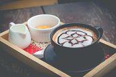 hot coffee with foam milk art. Black cup of coffee. Hot coffee in afternoon break. Coffee cup. coffee mocha on the wood desk. Coffee break.(selective focus vintage effect) poster