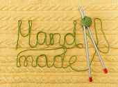 Yellow Knitted Background with Pattern and Braids;Grey Knitting Needle and Green Ball. Hand Made; Fancywork.Sign Hand-made from Thread poster