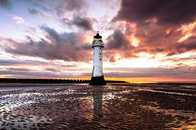 Wide angle view of Perch Rock lighthouse at New Brighton, near Liverpool in the UK. At sunset.