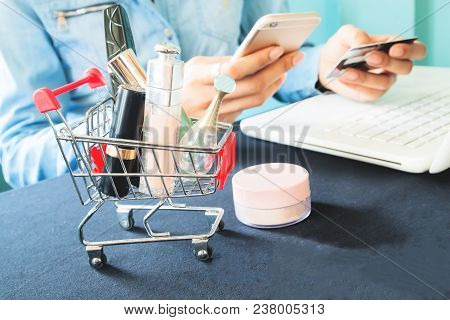 Woman's Items And Cosmetics In Shopping Cart, Woman's Hands Using Mobile Phone, Laptop And Credit Ca