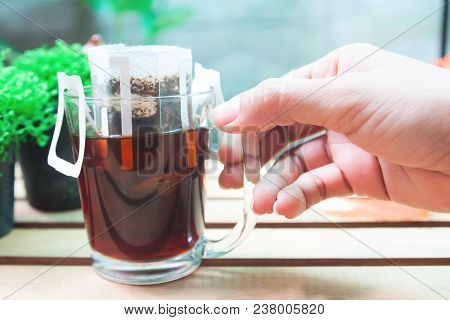 Close Up Woman's Hand With A Glass Of Drip Coffee,drip Bag Fresh Coffee With Garden View In Backgrou