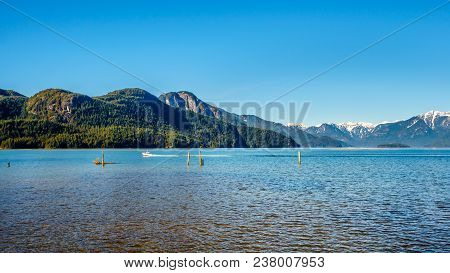 Fishing Boat On Pitt Lake With The Snow Capped Peaks Of The Golden Ears, Tingle Peak And Other Mount