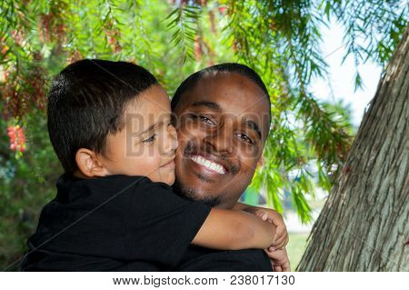 Young African American Dad Holding And Being Hugged By His Young Son.  The Boy Is Looking At His Dad