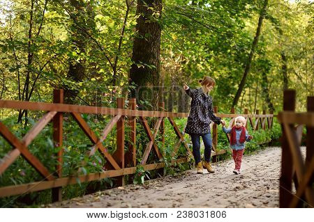 Little Boy With His Young Mother Talking During Stroll In The Forest. Active Family Time On Nature.