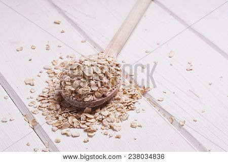 Heaped Rolled Oats Oatmeal Oat Flakes On Wooden Spoon On Rustic White Wooden Table